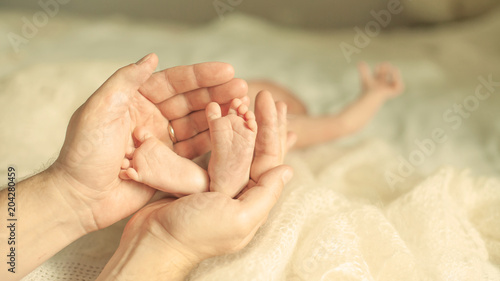 .happy mother hugging the legs of a newborn baby.