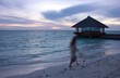 Young woman walking on the beach at sunset, motion blur effect, Maldives