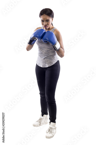 Black female on a white background wearing boxing gloves looking angry. Part of image set for gritty woman series.