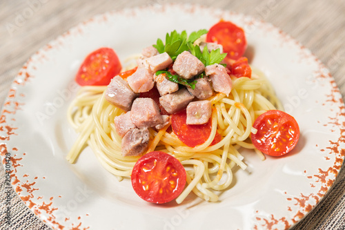 Spaghetti with sauce of Mediterranean tuna, Italian extra virgin olive oil, pepper, cherry tomatoes and a sprinkling of parsley © magati