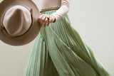 Hat, beige blouse and turqoise pleats skirt on light street backgraund.  Fashion and stylish concept. - 204318614