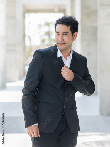 Fototapeta Happy Asian businessman standing in city with building background.