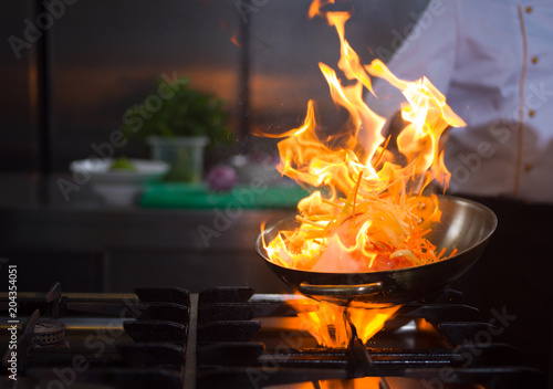 Chef doing flambe on food - 204354051