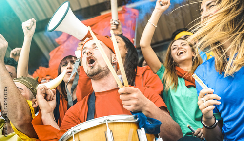 Fan supporters friends cheering and watching soccer cup match at intenational stadium - Young people group with multicolored tshirts having excited fun on football world championship sport concept