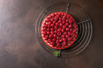 Red raspberry shortbread tart with lemon custard and glazed fresh raspberries served on cooling rack over dark brown texture background. Top view, copy space.
