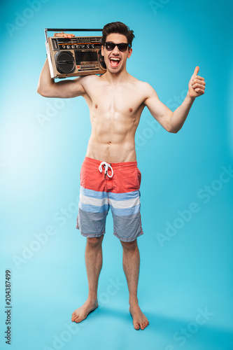 Full length portrait if a cheerful shirtless man