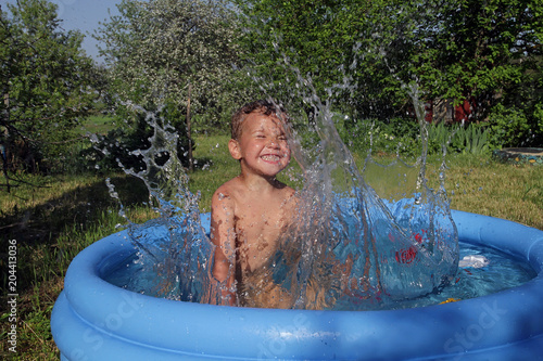 the little boy is very emotionally playing and laughing laps with the water in the children's pool of blue.