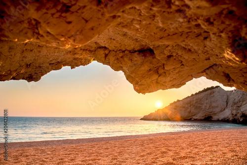 Piękny, spektakularny widok z jaskini na zachód słońca na plaży, wyspa Lefkada, Porto Katsiki. Grecja