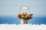 flowers basket with Welcome title, clouds and blue sea background
