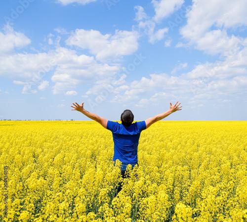 Plexiglas Geel Free man in the field. The man raised his hands up. Field of flowering rape.