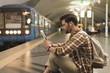 Quadro side view of young man with digital tablet and earphones sitting on floor at subway station