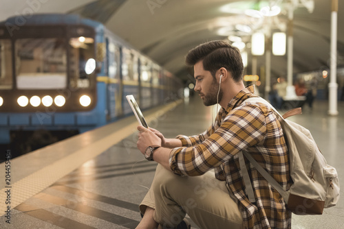 Sticker side view of young man with digital tablet and earphones sitting on floor at subway station