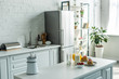 Quadro interior of modern light kitchen with fridge and kitchen counters