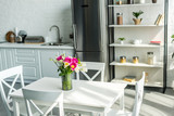 interior of modern light kitchen with bouquet on wooden table
