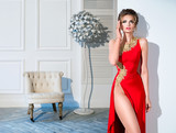 Beautiful woman in red dress in the room