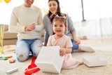 family, holidays and people concept - mother, father and happy little daughter with gift box at home birthday party - 204490434