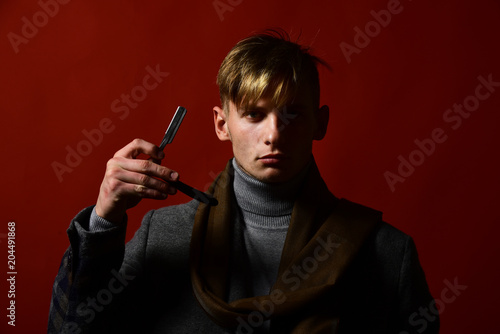 Man in vintage style holds razor blade in his hand.