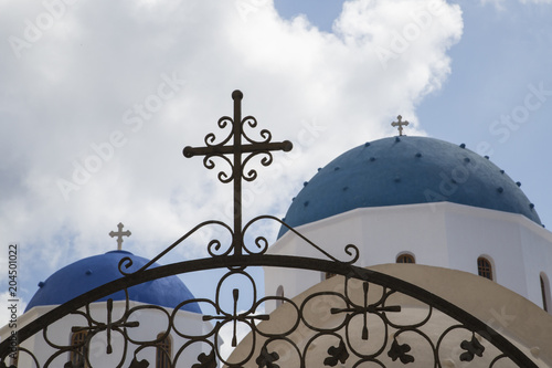 Fotobehang Santorini wrought-iron gate with cross in front of domed church chapel