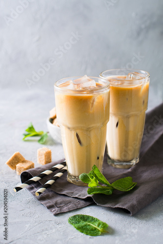 Wall mural Iced coffee in tall glasses with cream and pieces of sugar, mint and straw