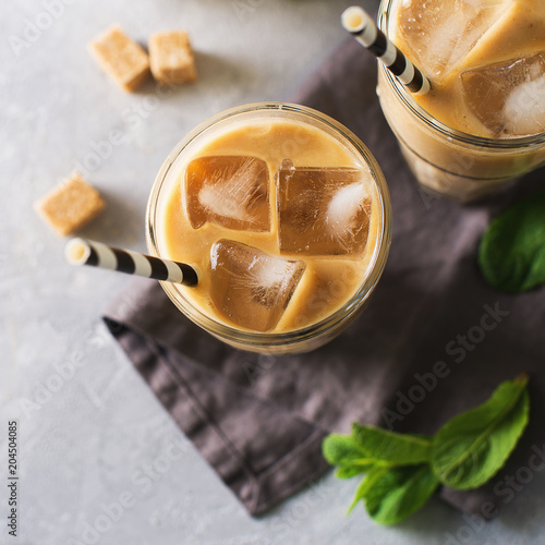Poster Iced coffee in tall glasses with cream and pieces of sugar, mint and straw