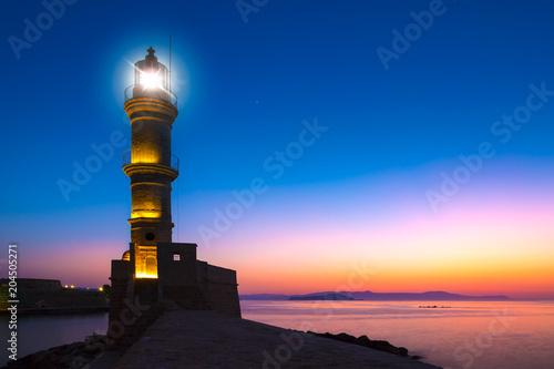 Fotobehang Vuurtoren A beautiful night sky behind a shining lighthouse. Chania, Crete, Greece