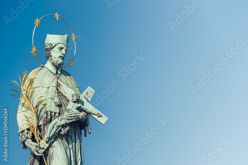 Figure of Saint with cross at Old Town Charles (Karluv most) Bridge Tower in Prague, Czech Republic - 204506264