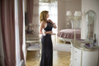 Quadro Fashionable lady dressed in evening black lace dress. Young woman posing in sensual pose holding pink fluffy handcuffs in a room with exquisite interior.
