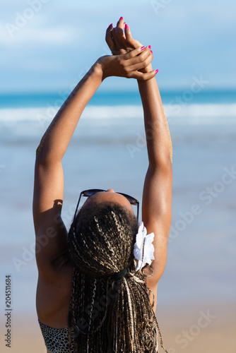 Poster Back view of black woman with summer braids enjoying and relaxing on vacation at the beach. Female in fashionable ethnic bikini.
