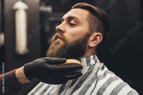 Hipster young good looking man visiting barber shop. Trendy and stylish beard styling and cut. © hedgehog94