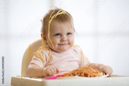 Little baby girl eating her lunch and making a mess - 204538083