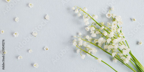 Aluminium Lelietjes van dalen Lily of the valley on a blue paper textured background. Pattern of small flowers of the may-lily. Abstract floral background.Top view, flat lay. March 8, mother's day background.