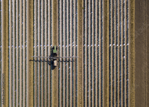 Aluminium Trekker Straight down view of tractor spraying chemical fertilizer or pesticide on a tomato field.