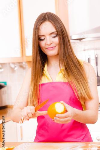 Woman peeled orange fruit with knife