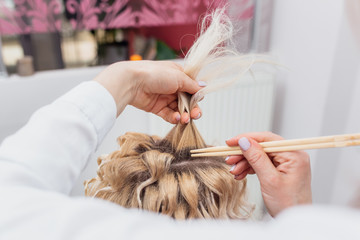 Hairdressers hands drying long blond hair with blow dryer and round brush © alexandrumusuc