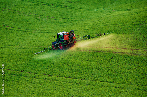 Aluminium Trekker Farm machinery spraying insecticide to the green field, agricultural natural seasonal spring background