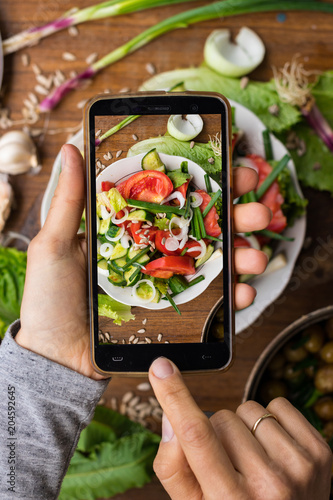 Phone photography of food. Woman hands take photo of lunch with smartphone for social media. Fresh vegetables salad. Raw vegan vegetarian healthy dinner  - 204592645