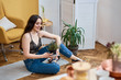 Stylish young woman sitting on floor in living room, smiling and holding flowers in hands