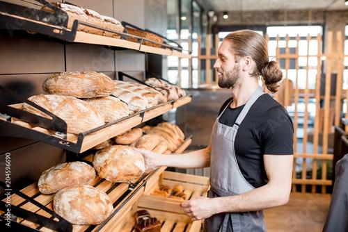Fototapeta Seller working in the bakery shop