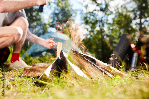 Young scout cutting firewood for campfire on grass during trip on summer day