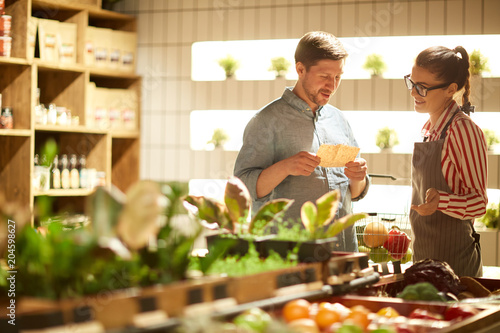 Polite shop assistant talking to one of visitors of supermarket and giving him advice about what to choose