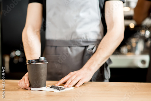 Barista holding coffee cups indoors
