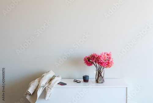 White sideboard with pink dahlias, coffee, glasses, smart phone and jacket against neutral wall background with copy space