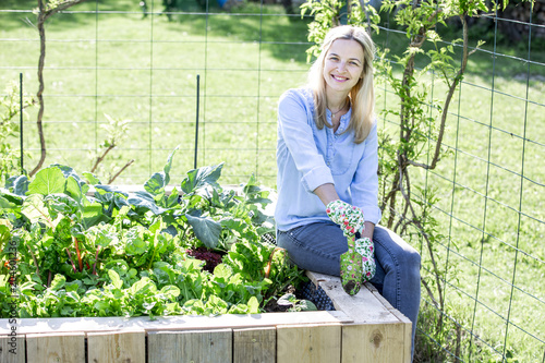 Happy woman is proud of her own raised bed