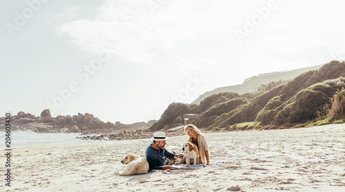Fototapeta Senior couple relaxing on beach with pet dogs