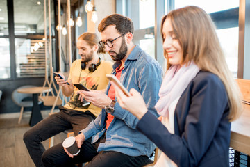 Young people using smartphones in the cafe