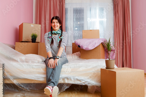 Photo of happy woman sitting on sofa among cardboard boxes