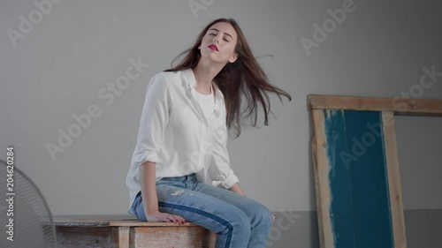 woman in industrial studio wears jeans and white shirt blowing long hair rose bright lips. Classick jeans outfit. Sits on wooden table