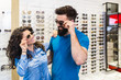 Happy young couple choosing together sunglasses in optical store.