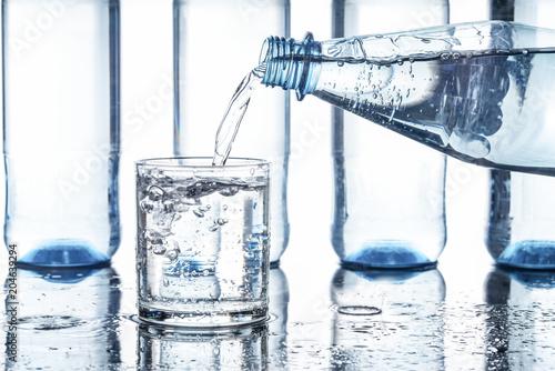 Woda mineralna wlewa się do szklanki, białe tło
