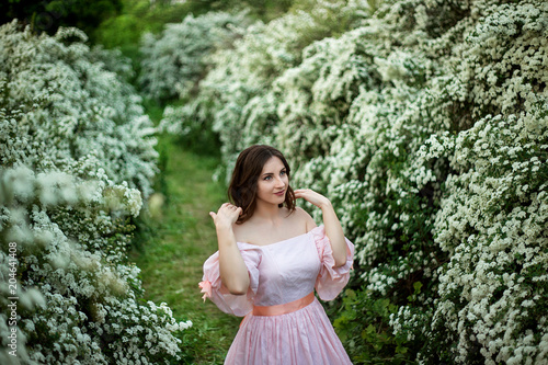 Aluminium Olijf beautiful girl in a smart dress on the background of flowering bushes